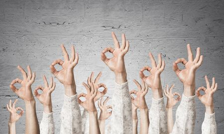 Row of man hands in white sweater showing okay gesture. Agreement and approval group of signs. Human hands gesturing on background of grey wall. Many arms raised together and present popular gesture. Stock Photo