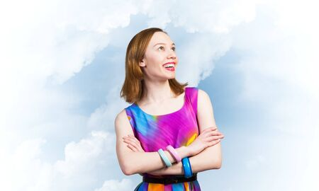 Smiling woman standing with folded arms and looking up aside. Elegant good looking lady wears bright dress and bracelets. Joyful redhead girl with perfect teeth smile on blue sky background.