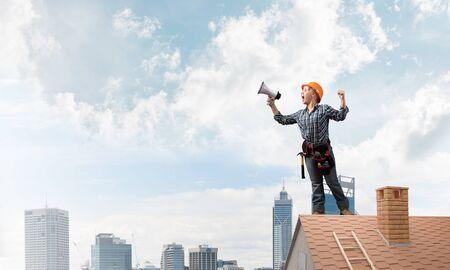 Ekspresyjna kobieta w kasku ochronnym i odzieży roboczej krzyczy do megafonu. Młody emocjonalny pracownik budowlany z szeroko otwartymi ustami stojący na ceglanym dachu budynku. Zapowiedź nowości i reklama
