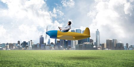 Happy aviator driving small propeller plane. Modern business center with high skyscrapers on background. Man in airplane flying low above ground. Megalopolis panorama with green grass in sunny day