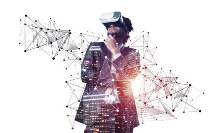 Handsome young man standing with VR headset. Businessman wearing VR goggles and exploring virtual reality. Caucasian businessperson in formal wear against white background. Enjoying new experience.