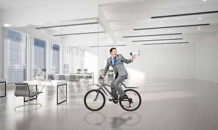 Man in business suit riding bicycle at conference hall. Businessman with megaphone looking back on bike at loft office interior with panoramic windows. Business presentation and announcement.