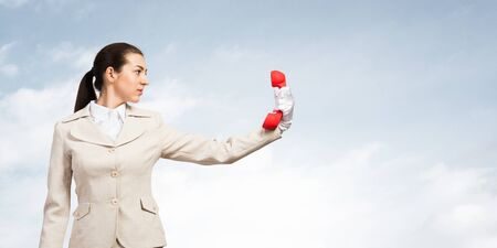 Businesswoman holds vintage red phone on distance. Serious operator in business suit posing with telephone on blue sky background. Employee ignores communication. Business assistance and support. Banco de Imagens