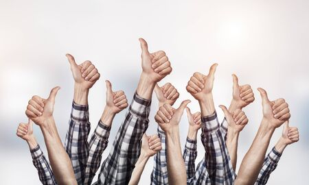 Row of man hands showing thumb up gesture. Agreement and approval group of signs. Human hands gesturing on light blurred background. Many arms raised together and present popular gesture. Stock Photo