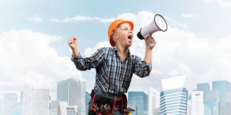 Expressive woman in safety helmet shouting into megaphone. Portrait of young emotional construction worker with loudspeaker on background of modern city. News announcement and advertisement.