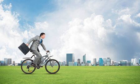 Young man riding bicycle on green grass. Businessman on bike hurry to somewhere. Corporate employee in grey business suit with suitcase on cycle outdoor. Male cyclist on green meadow at sunny day