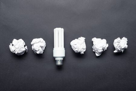 Fluorescent lamp and crumpled white paper balls on black background. Idea generation and brainstorming motivation. Business concept of successful and failing ideas. Creative and genius solutions Stock Photo