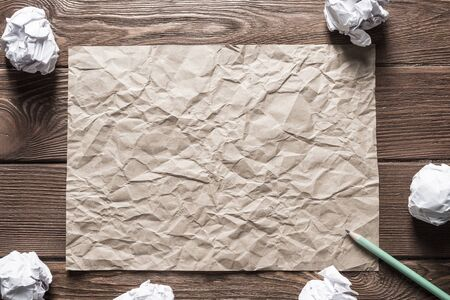 Crumpled brown paper sheet and pencil on wooden table