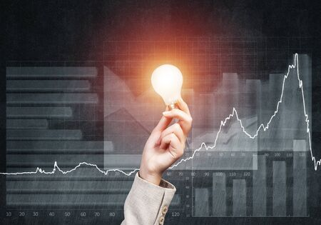 Business woman hand with glowing incandescent lamp on background grunge wall. Successful business solution concept with electric light bulb. Financial management and investment strategy planning Фото со стока - 131318981