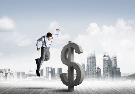Young furious businessman going to crash with fist stone dollar symbol Banco de Imagens - 131327867