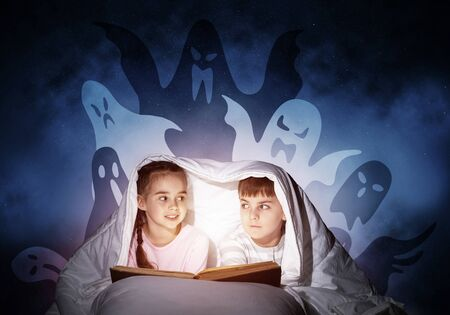 Scared girl and boy reading kids book in bed. Frightened children lying under blanket together. Kids in pajamas and funny ghosts silhouettes back on night sky. Children reading magic fairy tales Foto de archivo - 131360820