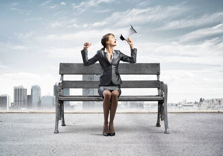 Business woman with megaphone sitting on wooden bench. Female speaker shouting in loudspeaker outdoors. Modern cityline panorama with cloudy sky. Business marketing and announcement.