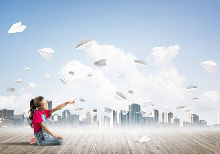 Cute kid girl sitting on wooden floor and paper planes flying around