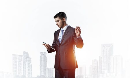 Businessman with documents pointing away on white background. Front view of standing entrepreneur in business suit and tie. Successful business person in formal wear gesturing on copy space.