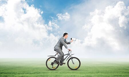 Businessman with megaphone in hand on bike at sunny day. Promotion and announcement. Corporate employee in business suit riding bicycle on green meadow. Handsome cyclist on background of blue sky.