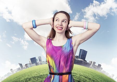 Redhead beautiful girl closed her ears with hands. Joyful lady with charming smile in colorful dress and bracelets on background modern town panorama. Portrait of happy young woman looking up aside.