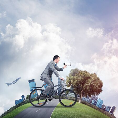 Businessman with megaphone in hand on bike. Corporate employee announcing in loudspeaker. Man in business suit riding bicycle on road. Handsome cyclist and world round panorama of modern downtown