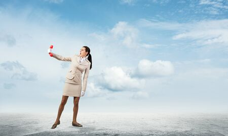 Young woman looks scared at retro phone in her hand. Fearful secretary in white business suit with phone standing on road outdoor. Hotline support service. Business assistance and consultation concept
