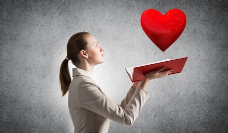 Beautiful woman showing red heart above opened notebook. Love and tenderness, valentines holiday concept. Elegant girl in white business suit with open book on background of grey wall. Foto de archivo - 131361400
