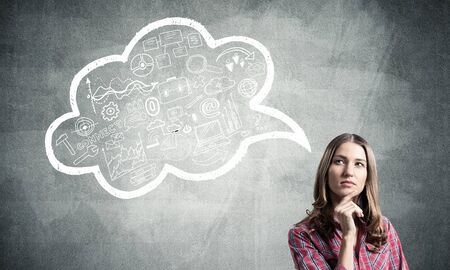 Serious woman looks pensive upwards and thinking something. Speech bubble full of business diagrams doodles on grey wall. Puzzled girl has serious facial expression. Woman wears red checkered shirt Stockfoto