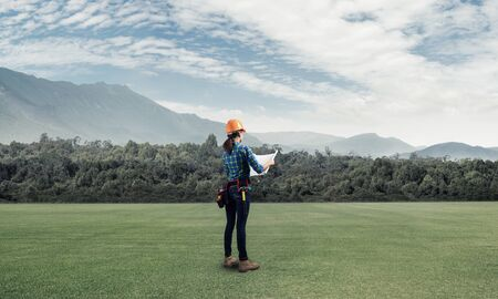 Young woman in safety helmet standing on green field with blueprints. Back view of female architect in workwear checking new construction site at countryside. Industrial engineering and construction Foto de archivo - 131361404