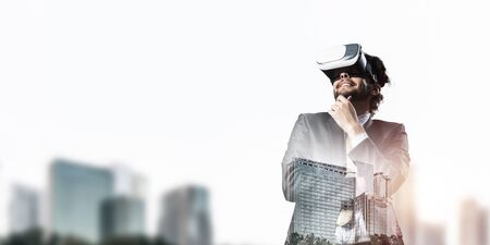 Young handsome businessman in virtual helmet against cityscape background Foto de archivo - 131361408