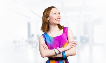 Smiling woman standing with folded arms and looking up aside. Elegant good looking lady wears bright dress and bracelets. Joyful redhead girl with perfect teeth smile on blurred office background.