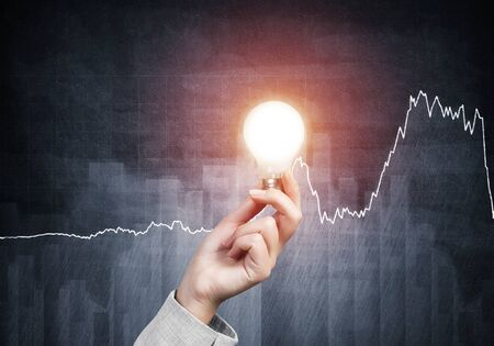 Human hand with glowing incandescent lamp on grunge background with business infographics. Organization and motivation concept. Online professional business statistics and analytics.