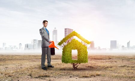 Businessman watering green plant in shape of house in desert. Green and eco friendly technology. Business development to success. Real estate company growth. Nature landscape with dry soil.