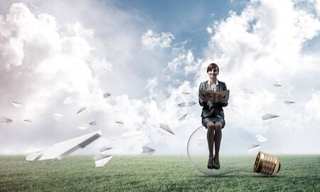 Young woman holding open book and sitting on big light bulb. Beautiful girl in business suit looking friendly on green field with flying paper planes. Business education and career development.