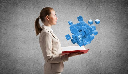 Woman showing geometric 3d blue cubes composition. Digital technology and innovation solutions. New approach to business management concept. Businesswoman with open book on background of grey wall. Stok Fotoğraf