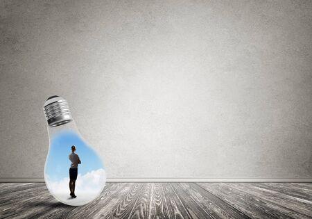 Businesswoman inside of light bulb in empty concrete room Foto de archivo - 131361504