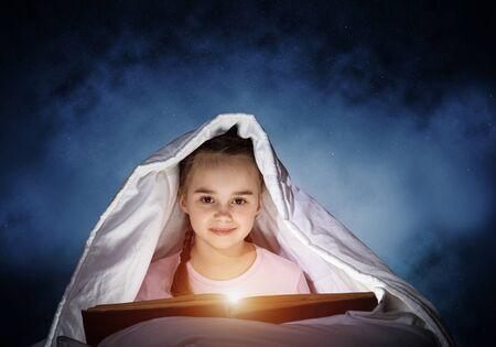 Happy little girl reading interesting book in bed after bedtime. Beautiful child with flashlight hiding under blanket. Smiling girl in pajamas on deep blue sky background. Child reading fairy tales. Foto de archivo - 131361506