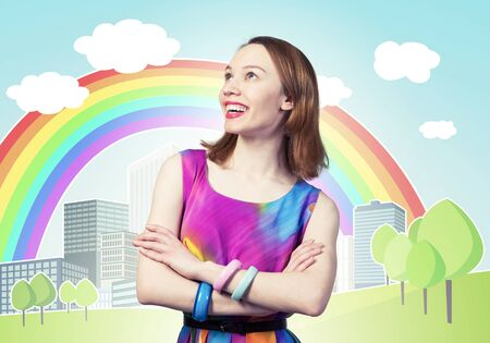Smiling woman with folded arms and looking up aside. Elegant fashionable lady wears bright dress and bracelets on background cartoon city with rainbow. Joyful redhead girl with perfect teeth smile.