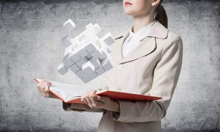 Woman showing geometric 3d white cubes composition. Digital technology and innovation solutions. New approach to business management concept. Businesswoman with open book on background of grey wall.