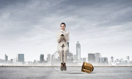 Attractive woman playing trumpet brass on background modern city. Young businesslady in white suit and gloves sitting on big light bulb with music instrument. Musician practicing and performing Stok Fotoğraf