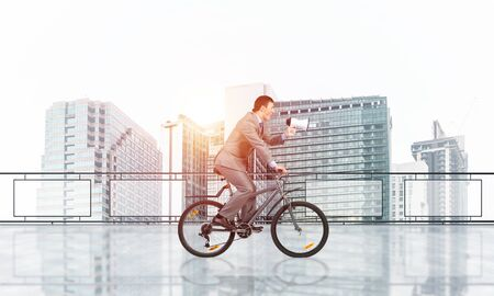 Businessman with megaphone in hand on bike. Promotion and announcement concept with copy space. Employee in business suit riding bicycle on balcony. Young cyclist on terrace with modern downtown view.