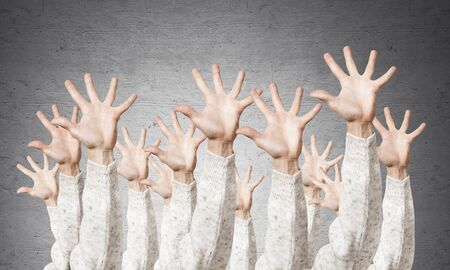 Row of man hands showing five spread fingers gesture. Hello or help group of signs. Human hands gesturing on background of grey wall. Many arms raised together and present popular gesture.
