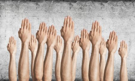 Row of man hands showing voting gesture. Participation and agreement group of signs. Human hands gesturing on background of grey wall. Many arms raised together and present popular gesture.