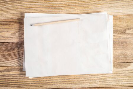 Sheet of paper lying on wooden table. Rectangular blank white old paper stack with pencil. Textured natural wooden background. Vintage copy space for design. Artist workplace and hand drawn skills Foto de archivo - 131363993