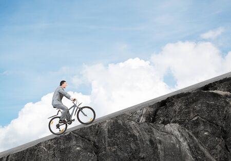 Businessman riding uphill by bike. Nature landscape with copy space. Man in business suit riding bicycle on mountain road. Cyclist on background of blue sky. Healthy lifestyle and outdoor activity Foto de archivo - 131363618