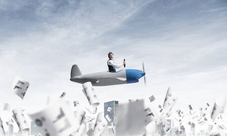 Successful management and information analysing concept with funny pilot. Aviator driving propeller plane above falling paper sheets with diagrams. Young man flying in small airplane above paperwork. Banco de Imagens