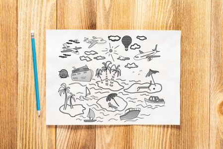 Summertime vacation at sea pencil hand drawn with group of traveling doodles. Tropical recreatiation and ocean cruising symbols on white page. Top view of workplace with paper on wooden surface. Imagens