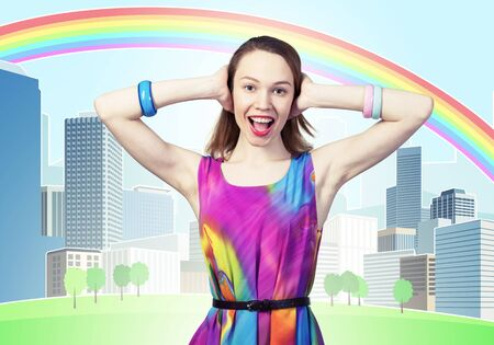 Redhead beautiful girl closing her ears with hands. Charming lady in bright colorful dress and bracelets on background cartoon cityscape. Portrait of happy young woman singing and smiling broadly