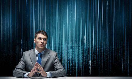 Giovane specialista in giacca e cravatta seduto alla scrivania. Tecnologia digitale per le imprese. Uomo su sfondo digitale astratto. Risorse umane nella moderna società Internet. Headhunting e gestione delle risorse umane Archivio Fotografico