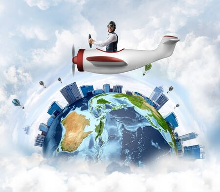 Businessman in aviator leather hat driving propeller plane. Traveling around the world by airplane. Funny man flying in small airplane in blue sky with clouds. Earth planet with modern cityscape.