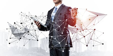 Businessman with documents pointing on abstract network composition. Entrepreneur in business suit and tie without face. Internet marketing and business development. Mixed media with virtual network