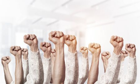 Row of man hands showing clenched fist gesture. Victory or protest group of signs. Human hands gesturing on light blurred background. Many arms raised together and present popular gesture.