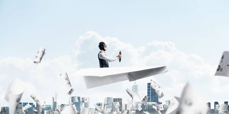 Businessman in aviator hat and goggles driving paper plane above cityscape. Papers falling down on background of blue sky with clouds. Expression pilot having fun in big paper airplane.