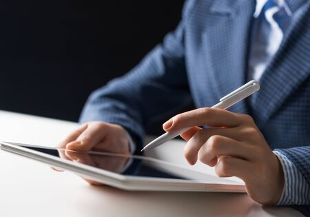 Man in business suit using tablet computer. Close-up of male hands holding pen and tablet gadget. Businessman at workplace in office. Business occupation and mobility, internet smart technology in job Banco de Imagens